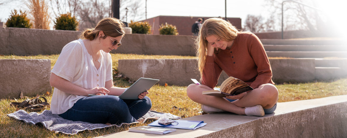 Two students studying outside on the Peace Mall