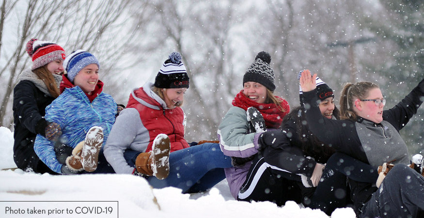 Central students sharing a sled in the snow. Photo taken prior to COVID-19.