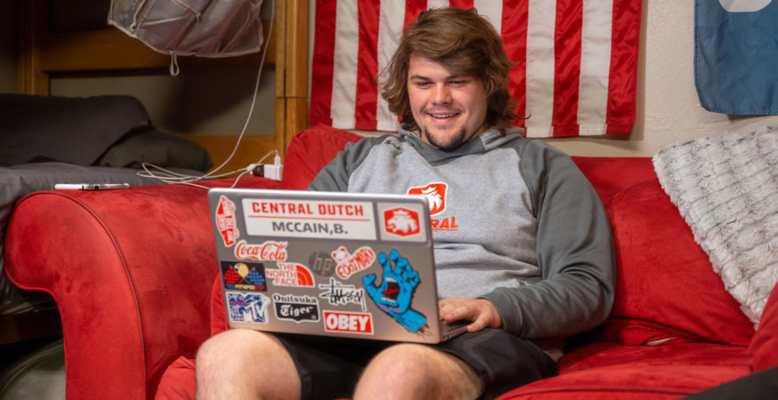 Student in his dorm room using a laptop.