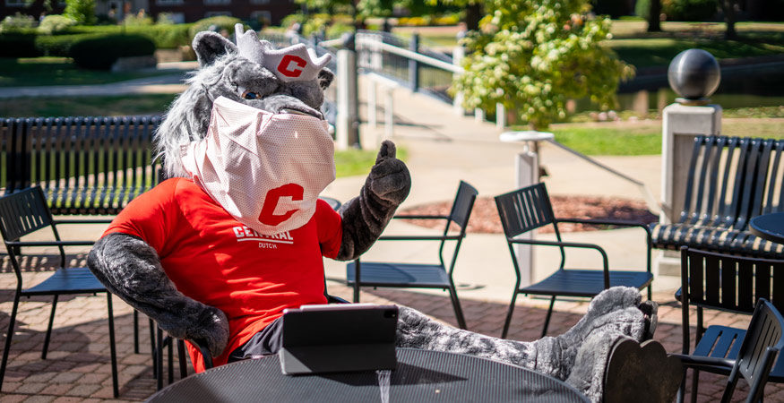 Central's mascot, Big Red, wearing a mask and giving a thumbs up to the camera