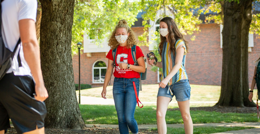 Two students walking across Central's campus while wearing masks.