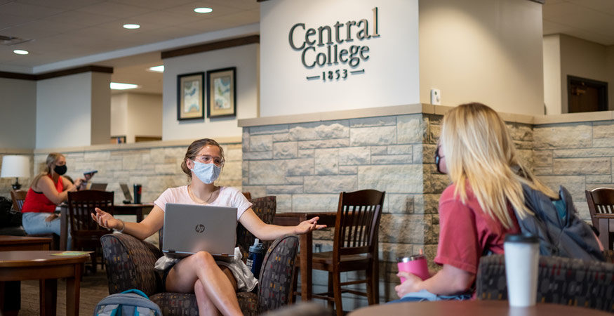Two masked students talking in Maytag Student Center.